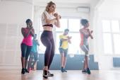 Alacsony látószögű kilátás fiatal multikulturális táncosok keresztbe tett kézzel teljesítő zumba a táncstúdióban