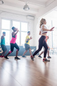 Multiculturális táncosok oldalnézete zumba mozgásokat képeznek a táncstúdióban