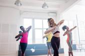Gyönyörű tréner, aki zumbát ad elő multikulturális táncosokkal a táncstúdióban