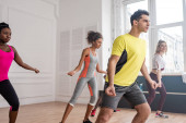 Fiatal többnemzetiségű táncosok a táncstúdióban, akik együtt gyakorolják a zumbát
