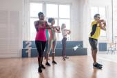 Oldalnézet jóképű edző gyakorló mozgását zumba multietnikus táncosok a táncstúdióban