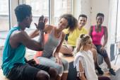 Szelektív fókusz mosolygó afro-amerikai zumba táncosok pacsizni, miközben pihen a táncstúdióban