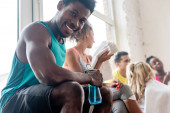 Selective focus of african american dancer holding sports bottle while smiling at camera in dance studio