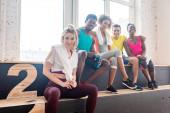Multikulturális zumba táncosok szelektív fókusza, akik a táncstúdió padján mosolyognak a kamera előtt