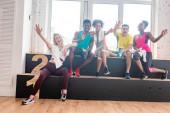 Mosolygó többnemzetiségű zumba táncosok köszöntik a kamera előtt a táncstúdióban