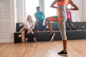 Szelektív fókusz a nő gyakorló multietnikus zumba táncosok padon a táncstúdióban