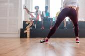 Szelektív fókusz a fiatal lány nyújtózkodó multietnikus zumba táncosok padon tánc stúdió