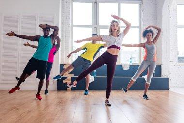 Multicultural zumba dancers practicing movements in dance studio