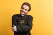 boldog katolikus pap néz kamera közben ölelés biblia elszigetelt sárga
