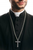 partial view of catholic priest in black cassock, with silver cross on necklace, isolated on white