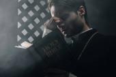 Fényképek fiatal gondolkodó katolikus pap megérintette arcát olvasás közben biblia közelében gyónási rács a sötétben a fénysugarak