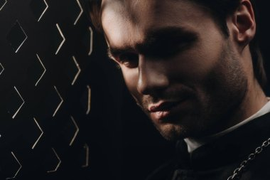 portrait of young tense catholic priest looking at camera near confessional grille in dark with rays of light