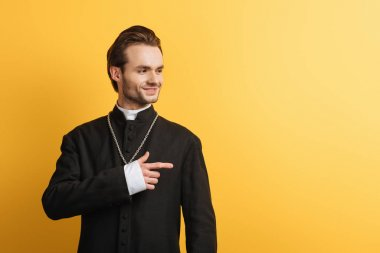 Smiling catholic priest looking away and pointing with finger isolated on yellow stock vector