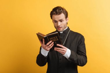Shocked catholic priest reading holy bible isolated on yellow stock vector