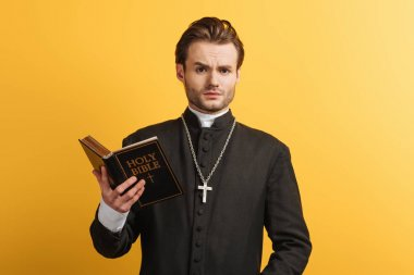 Surprised catholic priest looking at camera while holding bible isolated on yellow stock vector