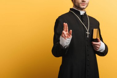 Partial view of catholic priest showing blessing gesture while holding bible isolated on yellow stock vector