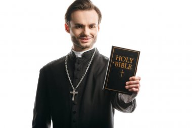 Young catholic priest smiling while holding holy bible isolated on white stock vector