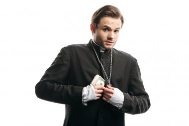 scared catholic priest looking at camera while hiding money under cassock isolated on white