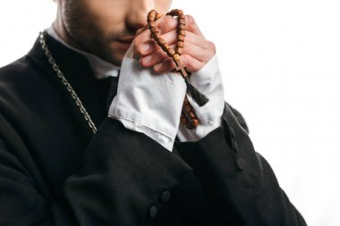 Partial view of catholic priest praying while holding wooden rosary beads near face isolated on white stock vector
