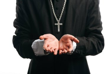Cropped view of catholic priest with silver cross on neck standing with cupped hands isolated on white stock vector