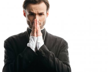 Serious, concentrated catholic priest praying while looking at camera isolated on white stock vector