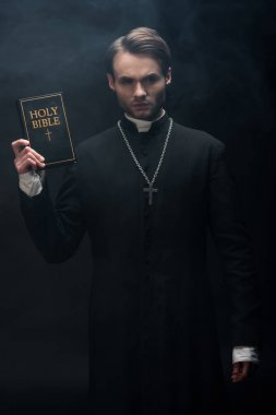 Young strict catholic priest showing holy bible at camera on black background with smoke stock vector