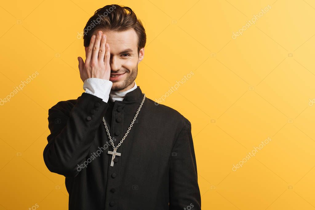 Smiling catholic priest covering eye with hand while looking at camera isolated on yellow stock vector