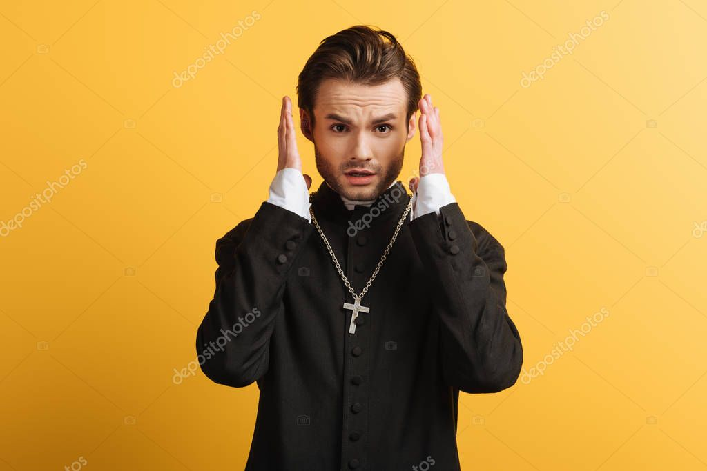 Shocked catholic priest holding hands near head and looking at camera isolated on yellow stock vector