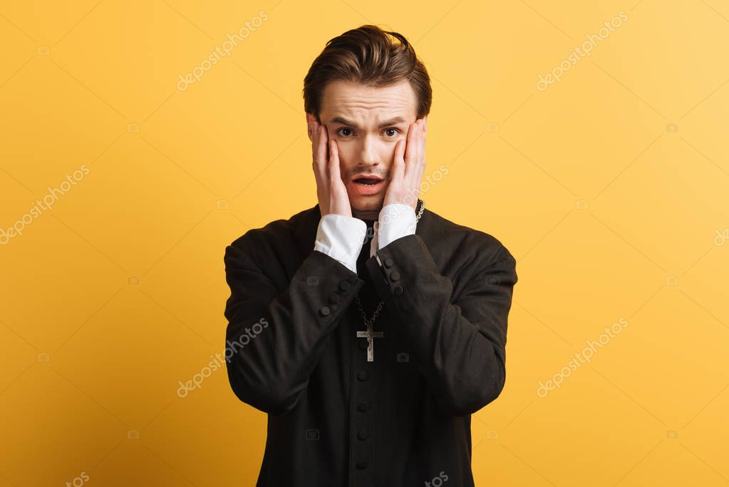 Shocked catholic priest touching face while looking at camera isolated on yellow stock vector