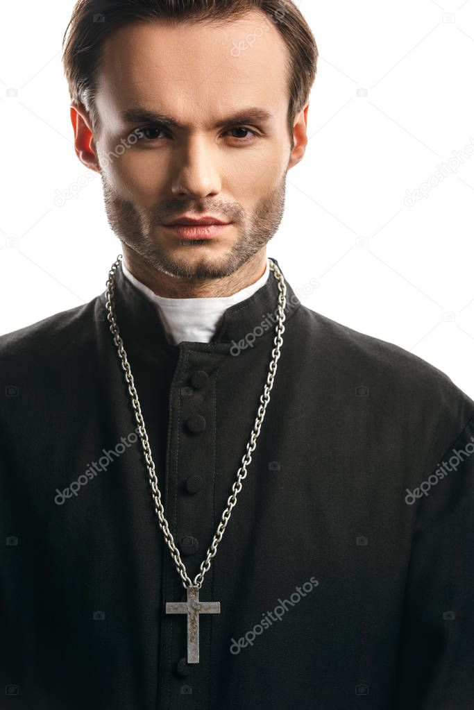 Young, concentrated catholic priest with silver cross on necklace looking at camera isolated on white stock vector