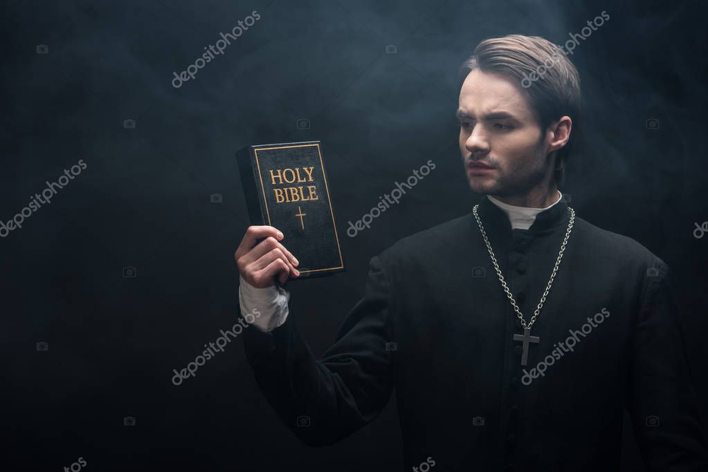 Thoughtful catholic priest looking at holy bible on black background with smoke stock vector