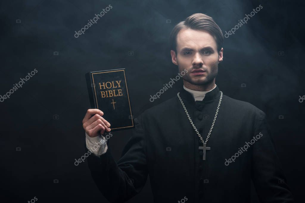 Young serious catholic priest showing holy bible at camera on black background with smoke stock vector