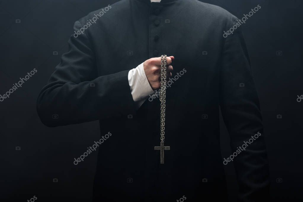 Cropped view of catholic priest holding necklace with silver cross isolated on black stock vector