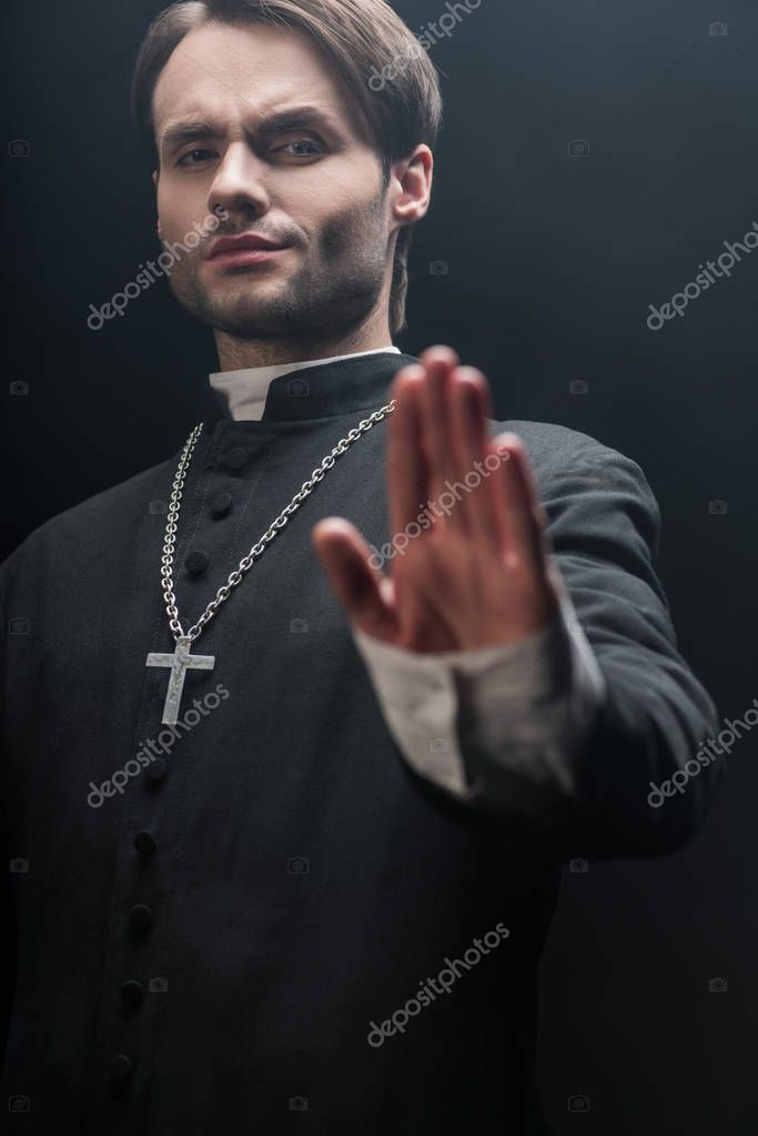 Low angle view of strict catholic priest showing refuse gesture isolated on black stock vector