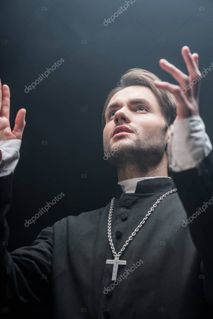 Low angle view of young serious catholic priest praying with raised hands isolated on black stock vector