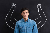 pensive young man with strong arms drawing on blackboard