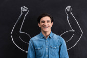 handsome smiling man with strong arms drawing on blackboard