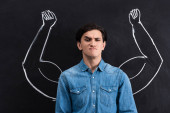 skeptical young man with strong arms drawing on blackboard