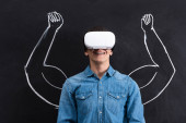 Fotografie happy young man using virtual reality headset, with muscular arms drawing on blackboard