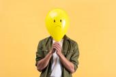 mladý muž drží smutný balón před obličejem, izolovaný na žluté