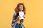 stresszes lány gazdaság digitális tabletta, elszigetelt sárga