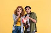 vystrašený pár sledující horor s kbelíkem popcornu, izolovaný na žluté