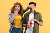scared girl watching movie while closing eyes to boyfriend with bucket of popcorn, isolated on yellow