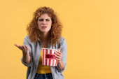 frustrated girl watching movie with bucket of popcorn, isolated on yellow
