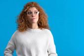 attraktive rothaarige interessierte Mädchen mit Brille, isoliert auf blau