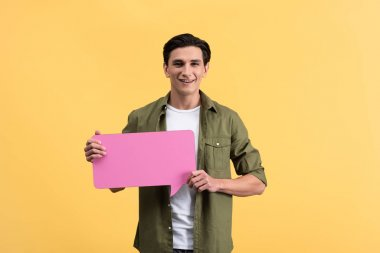 Smiling man holding pink speech bubble, isolated on yellow stock vector