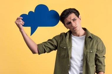 Sad man holding blue cloud speech bubble, isolated on yellow stock vector