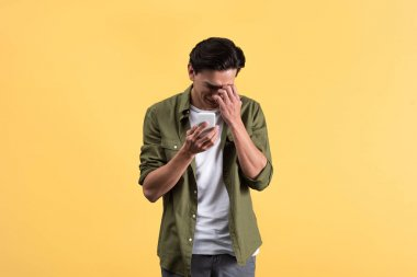 Emotional crying young man using smartphone, isolated on yellow stock vector