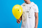 oříznutý pohled smutného muže držícího žlutý neklidný balón, izolovaný na modré