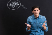 Fotografie stressed young man with shrug gesture, blackboard with thought bubble drawing behind
